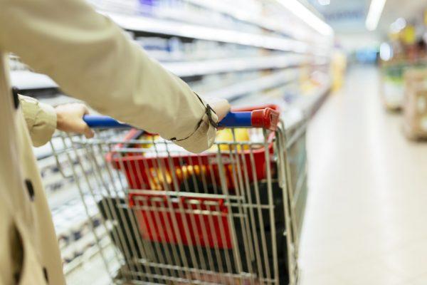 Woman pushing shopping trolley in modern supermarket